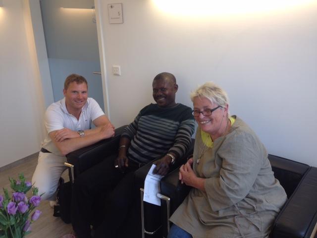 Links Augenarzt Dr Eckert in der Mitte ein Patient. Rechts Gabi Ayivi