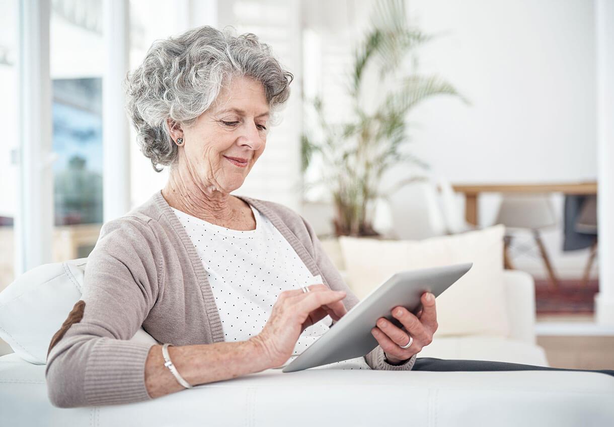 Ältere Frau, die auf ein Tablet schaut