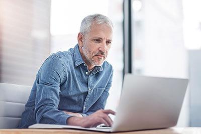 Mann sitzt vor Laptop