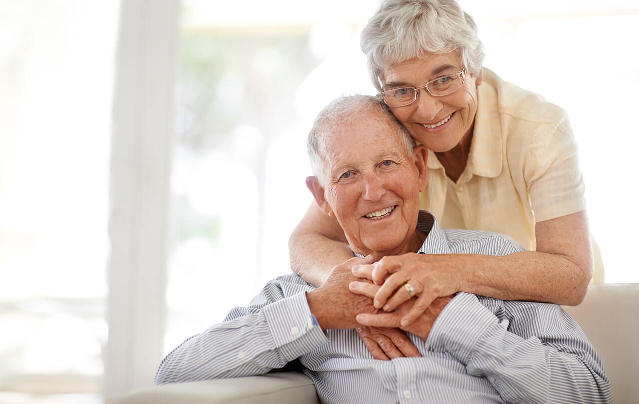 Portrait eines älteren Paares, dass sich umarmt und lächelnd in die Kamera schaut